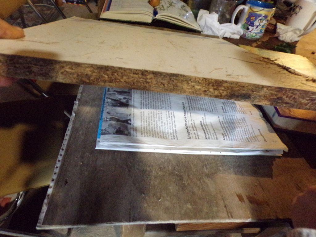 Une planche écrase le papier journal.